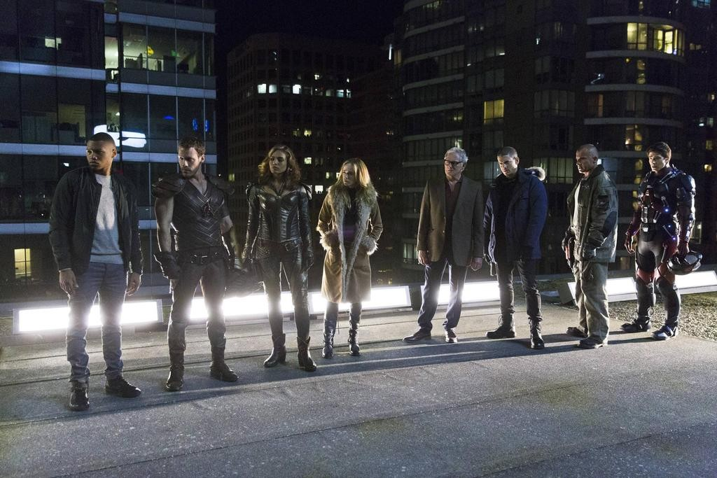 The cast of Legends of Tomorrow standing in a row on a rooftop at night.
