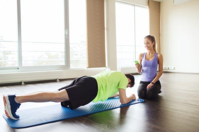 man performing a plank on a blue exercise mat as a woman times him