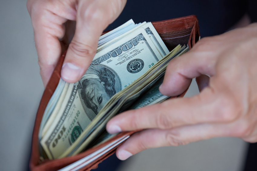 man looking into wallet filled with money