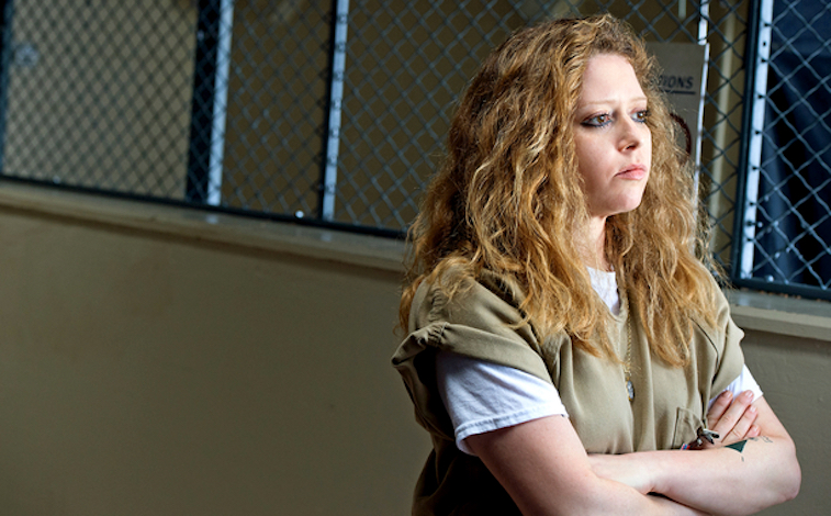 Natasha Lyonne as Nicky posing in a tan jumpsuit in front of a prison gate in Orange Is the New Black