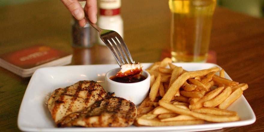A diner dips his entree in a tangy, zesty sauce