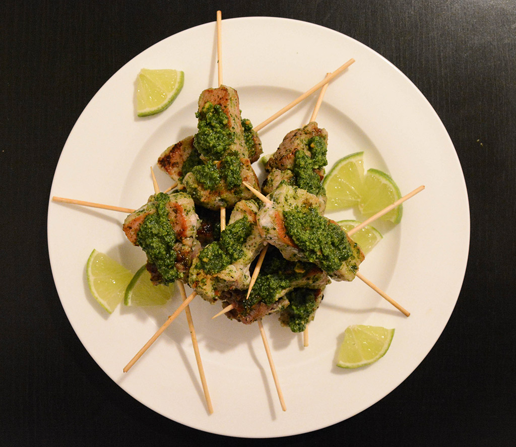 cilantro-peanut pork skewers on a white plate with lime wedges