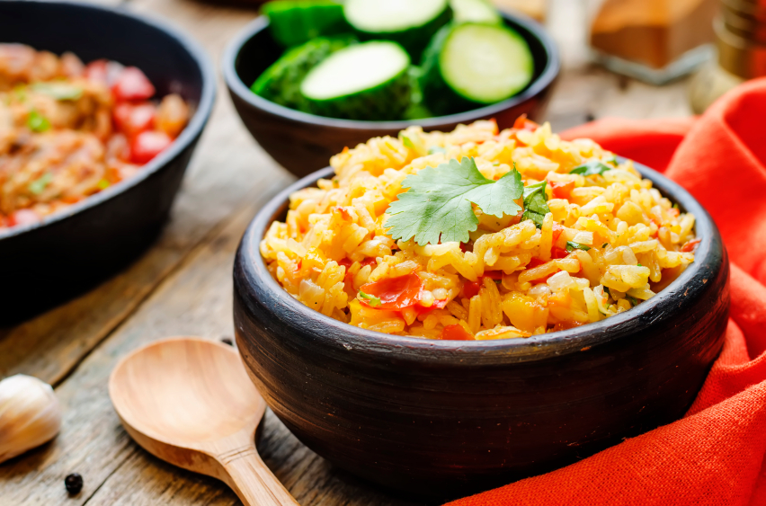 spanish rice with vegetables in a black bowl