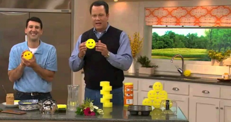 Two men are holding Scrub Daddy sponges in a fake kitchen.