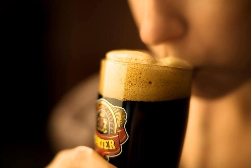 man drinking a glass of Sinebrchoff porter
