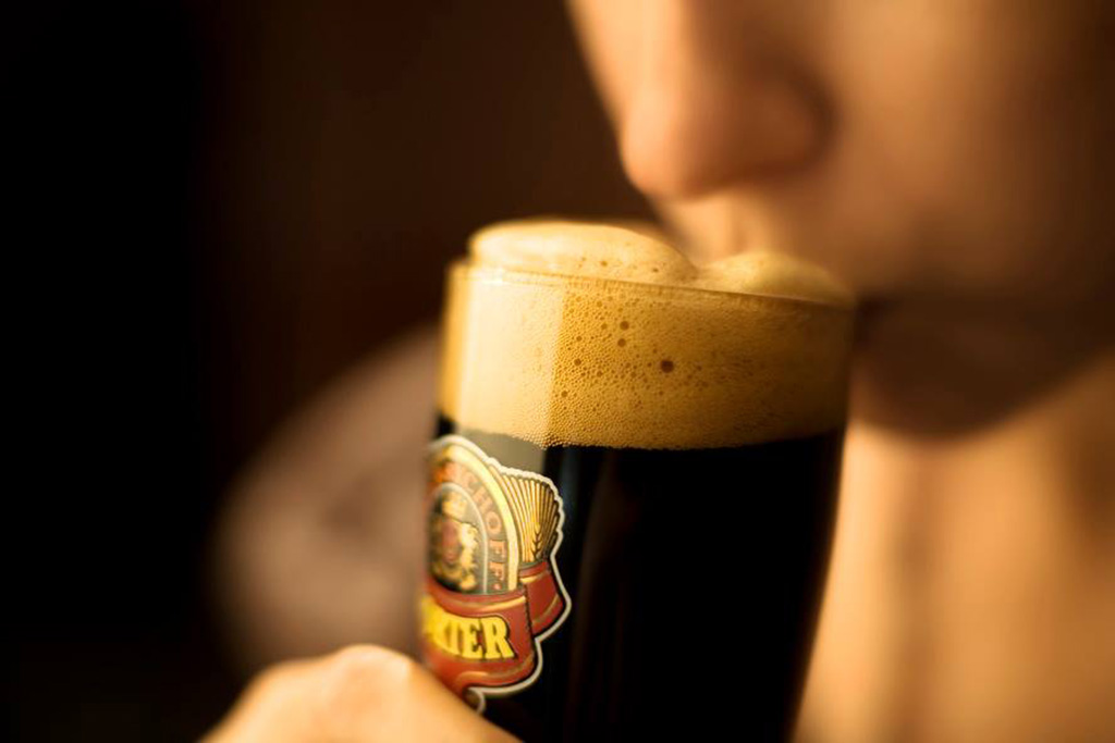 man drinking a glass of Sinebrchoff porter