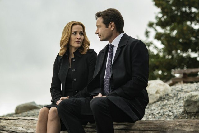 Gillian Anderson and David Duchovny sit next to each other on a long