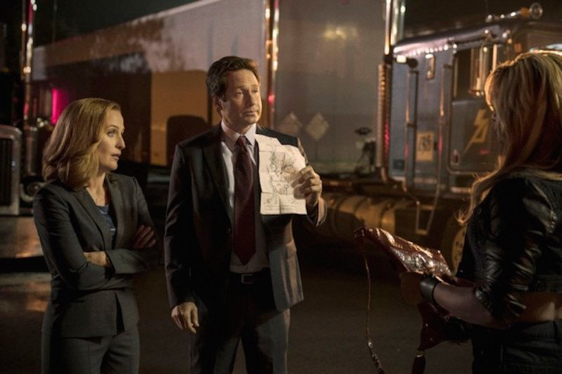 Gillian Anderson stands next to David Duchovny as he holds up a piece of paper