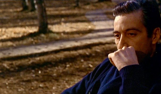 Al Pacino as Michael Corleone and sitting on a bench in The Godfather.