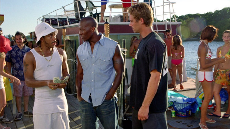 Ludacris, Tyrese and Paul Walker talk in a scene from 2 Fast 2 Furious