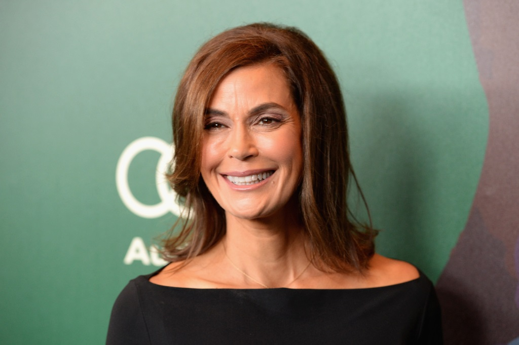 Teri Hatcher smiling on the red carpet, wearing a black dress