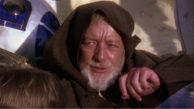 Alec Guinness in a brown robe sitting next to R2-D2.
