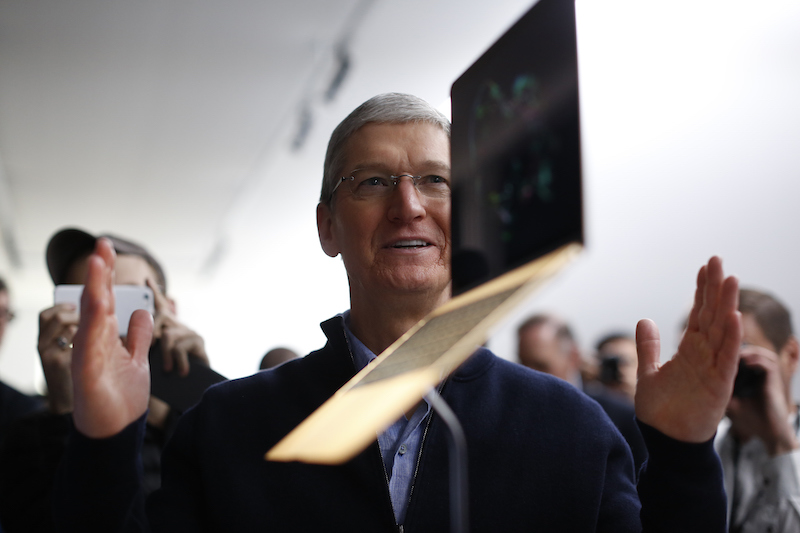 Tim Cook stands in front of a MacBook