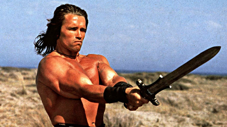 Arnold Schwarzenegger holds a sword in Conan the Barbarian