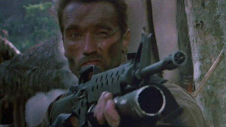 Arnold Schwarzenegger holds up a rifle in Predator