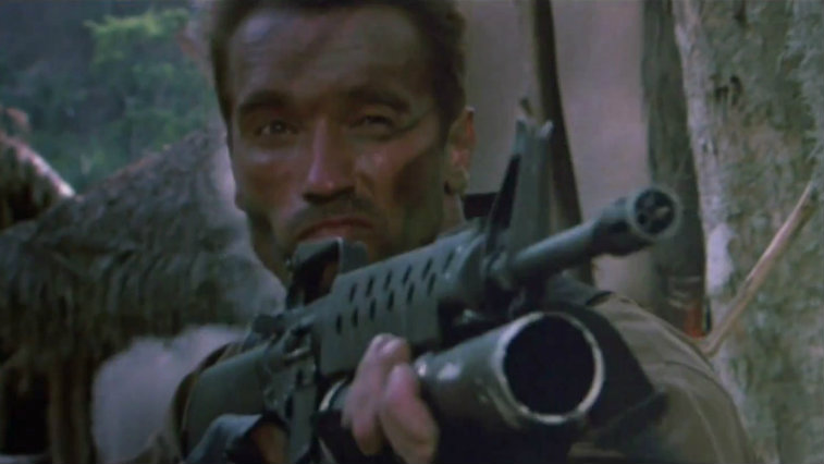 Arnold Schwarzenegger holds up a rifle in Predator