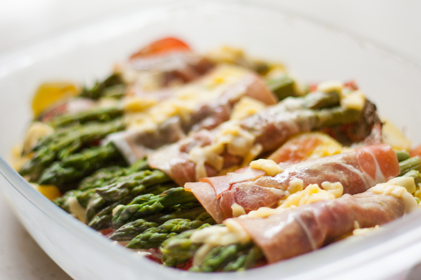 Prosciutto wrapped asparagus in a white tray