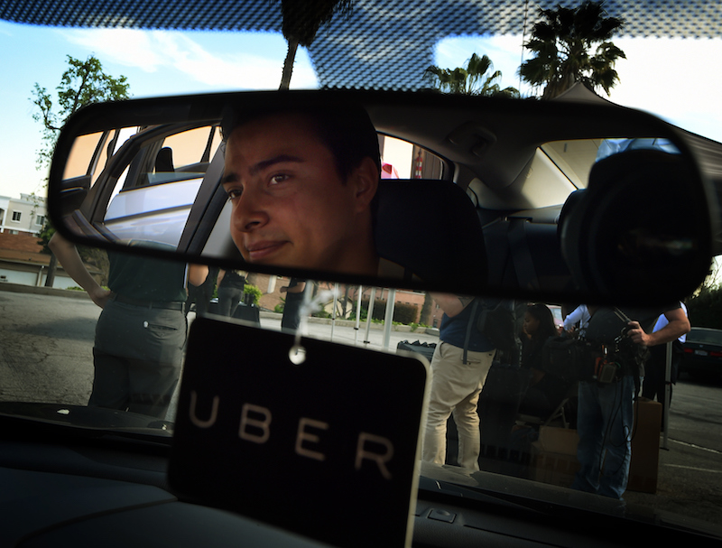 Jesse Vega checks a vehicle at the first of Uber's 'Work On Demand' recruitment events to recruit 12,000 new Uber drivers