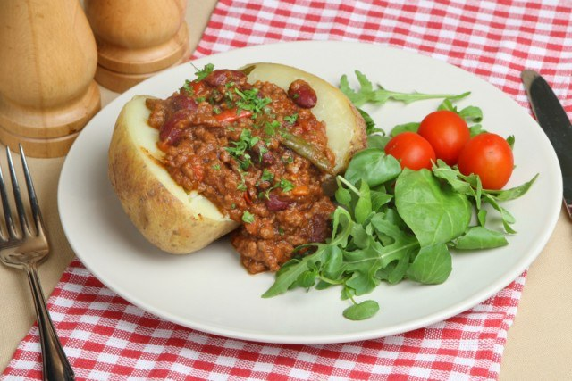baked potato topped with chili and served with a salad