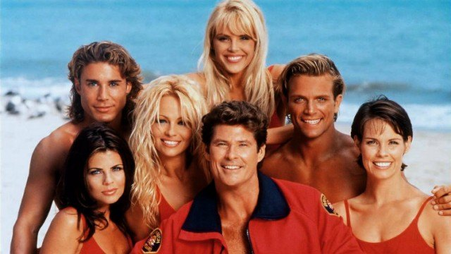 The cast of 'Baywatch' smiling and posing on the beach.