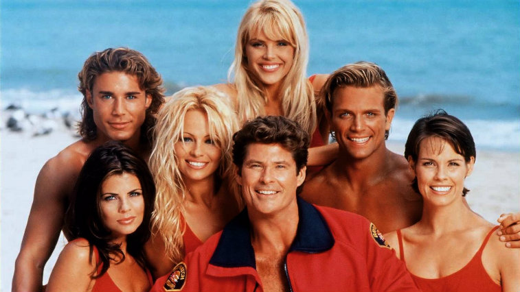 The cast of Baywatch smiling and posing on the beach