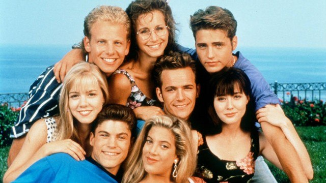 The cast of 'Beverly Hills, 90210' stands together in front of an ocean.