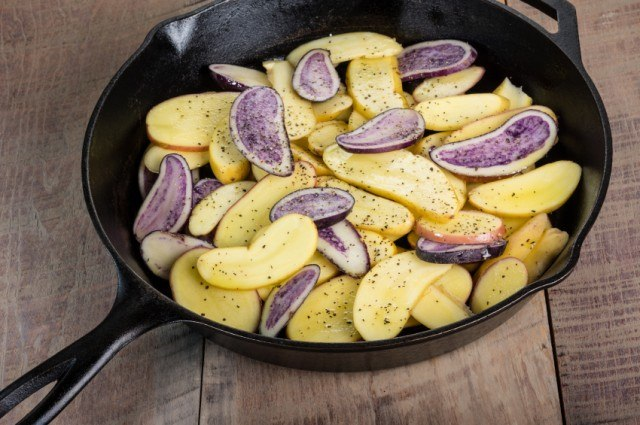 sliced fingerling potatoes with salt and pepper in a cast-iron skillet