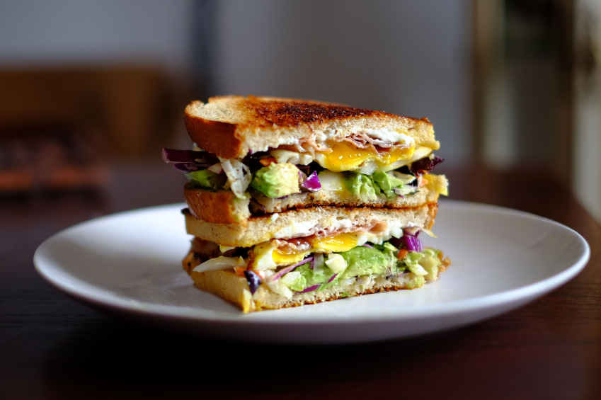 egg breakfast sandwich on toast with a runny egg