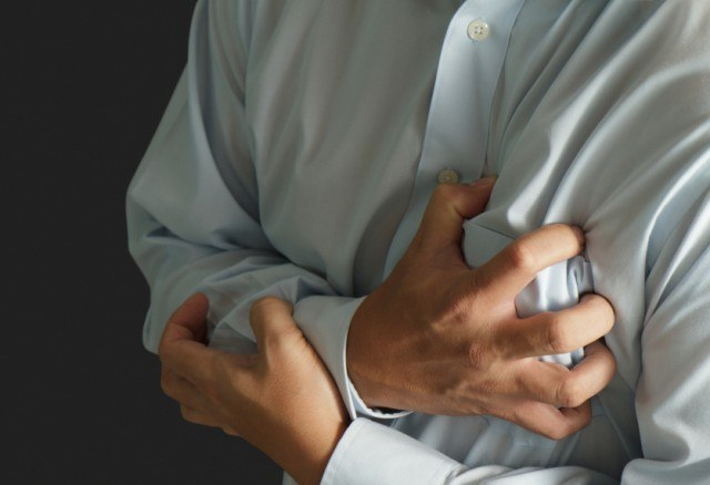 man clutching his heart in pain