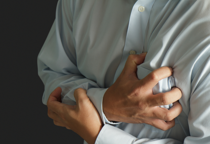 close-up of a man clutching his chest to show a heart attack