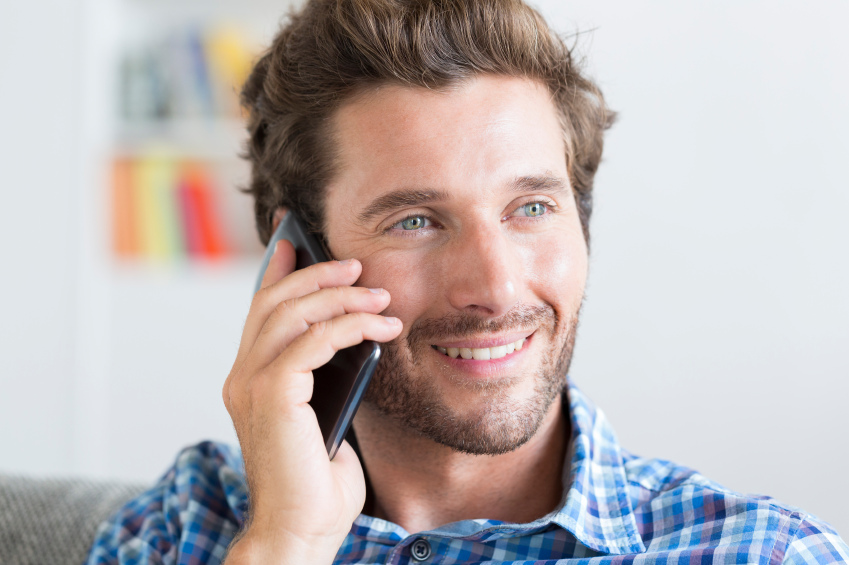 young man smiling and talking on a smartphone