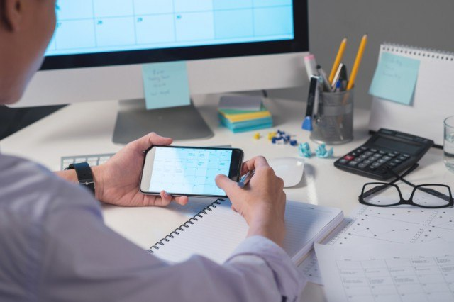 man checking calendar on a phone while at the office