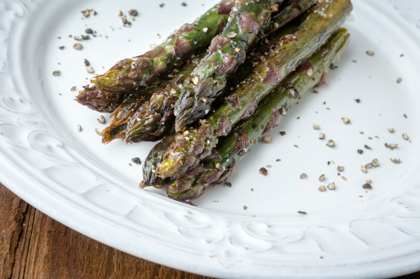 roasted asparagus with pepper on a white plate