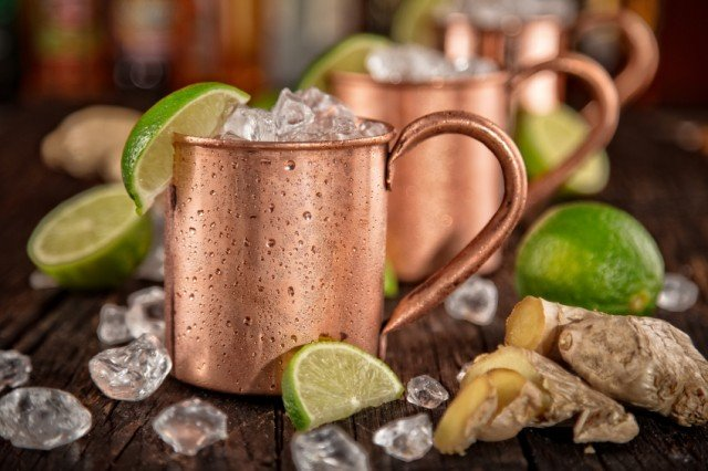 three Moscow mules in copper mugs in a row with ice and limes