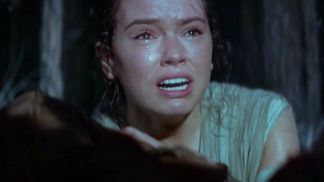 Daisy Ridley crying and hiding behind rocks.