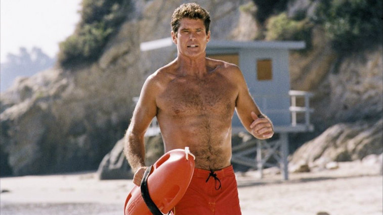 David Hasselhoff is running on the beach as a lifeguard.