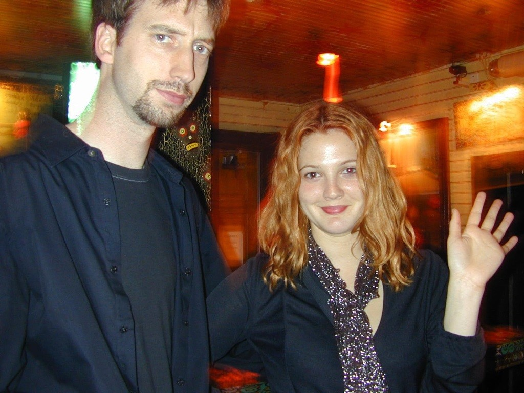 Drew Barrymore smiles and waves at the camera, while Tom Green looks on bemused