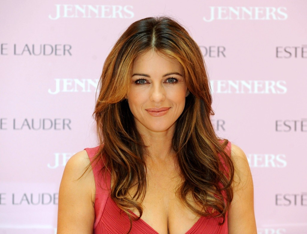 Elizabeth Hurley is smiling on the red carpet in a pink dress.