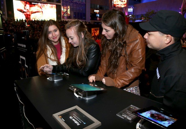People playing with tablets at a concert.