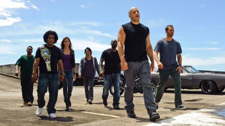 The cast of Fast Five walks away from their cars looking serious