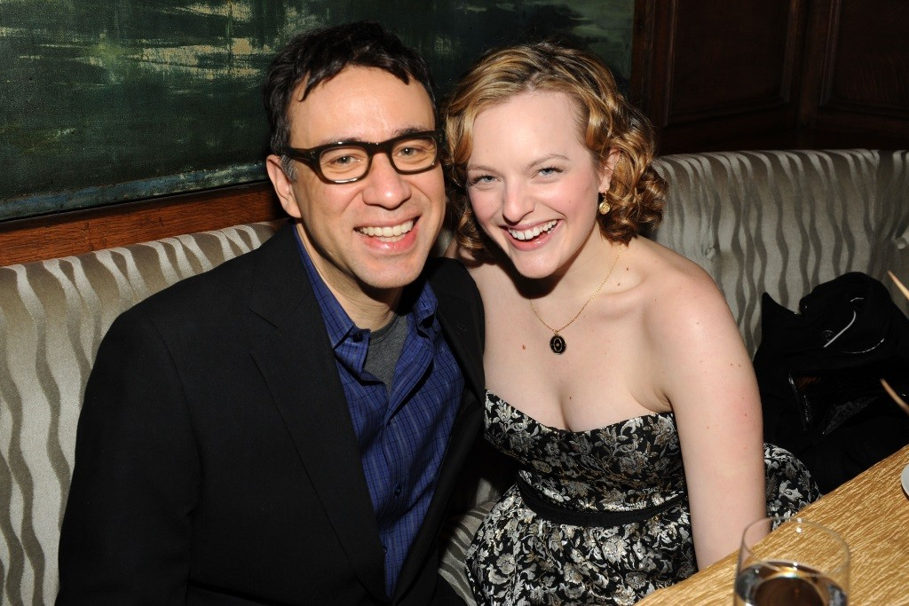 Fred Armisen and Elisabeth Moss sitting in a restaurant booth and smiling for the camera