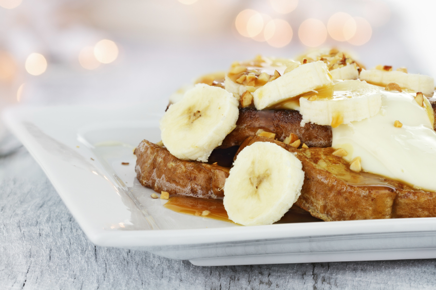French toast topped with bananas, toasted pecans and creamy caramel