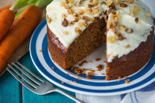Sliced carrot cake with cream cheese frosting and walnuts on a plate