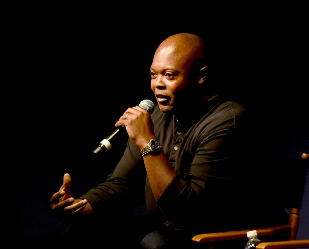 Cheo Hodari Coker sits on a chair and speaks in to a microphone.