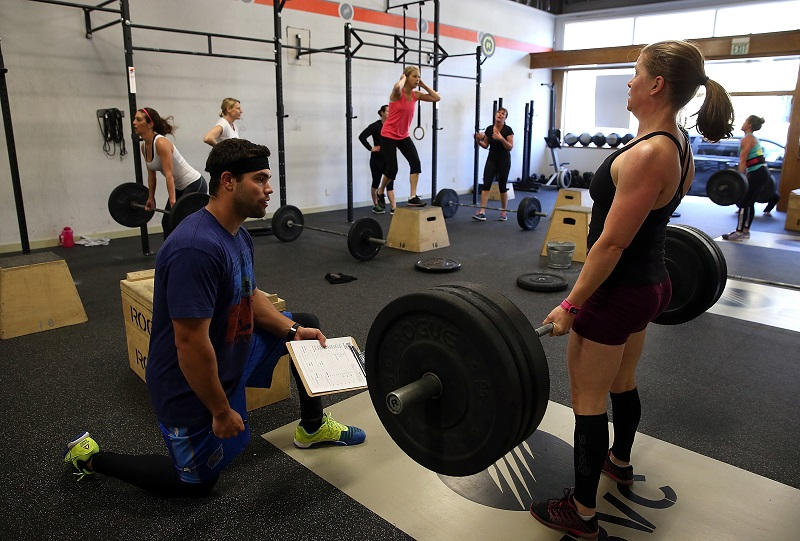 woman performs a deadlift while a trainer watches