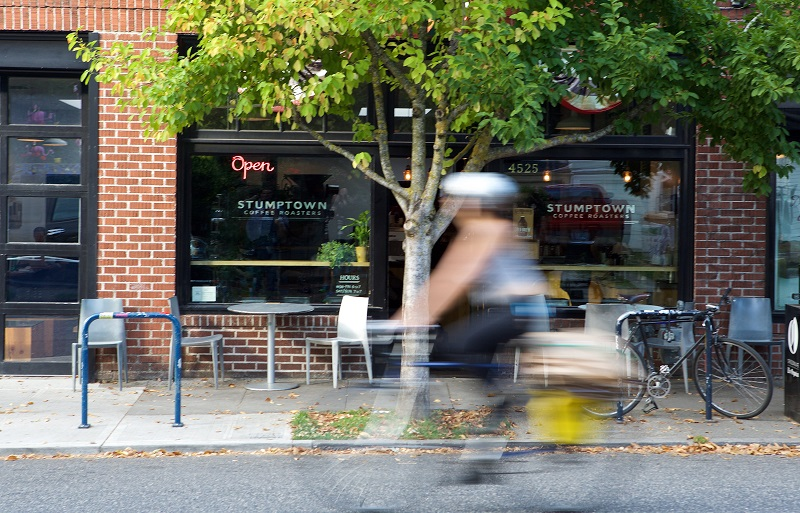 PORTLAND, OREGON - OCTOBER 6: A bicycle commuter rides past a Stumptown Coffee location on SE Division Street on October 6, 2015 in Portland, Oregon. Stumptown's owner and founder Duane Sorenson has confirmed that the company will be acquired by Peet's Coffee & Tea, according to published reports. Stumptown, which reportedly will operate independently after the aqcquisition, operates 10 stores in Portland, Seattle, New York and Los Angeles. (Photo by Craig Mitchelldyer/Getty Images)