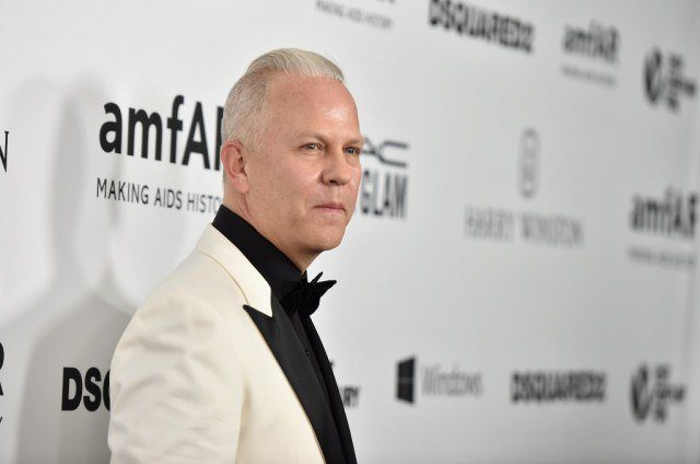 Ryan Murphy posing in a white suit and black bow tie.