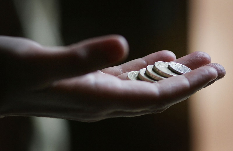 An outstretched hand containing loose change
