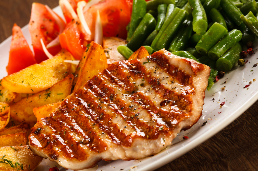 grilled pork chops with herbs served with potatoes and green beans