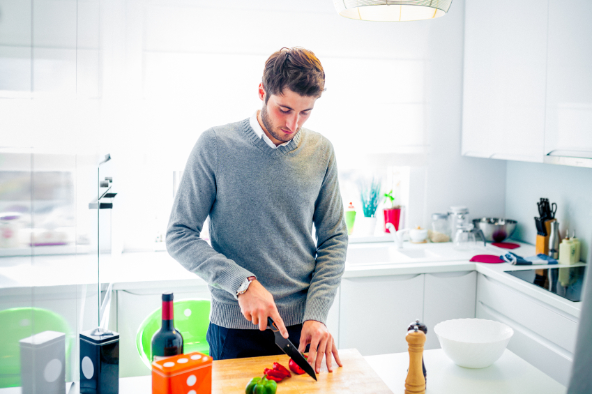 young man cutting vegetables in kitchen